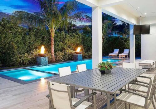 A glimpse of one of the views you can expect to find in the South Florida real estate expert Stephanie Kaufman's listed properties. A large swimming pool with palm trees on the edge is pictured.