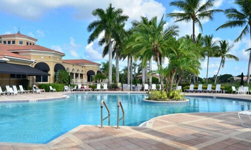 The view of a swimming pool from one of our Valencia Lakes homes for sale in Boynton Beach, FL