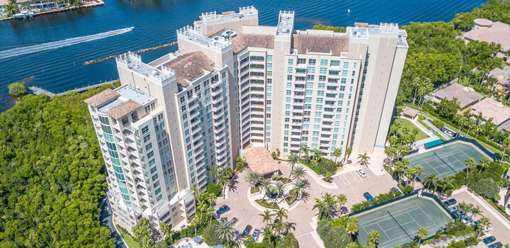 An aerial view of a condominium building in the highland beach area, close to the water.