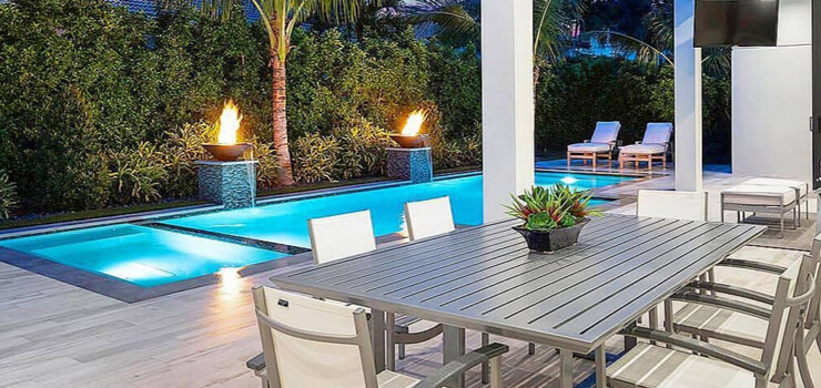 A glimpse of one of the views you can expect to find in the Valencia Shores homes for sale. A large swimming pool with palm trees on the edge is pictured outside the home.