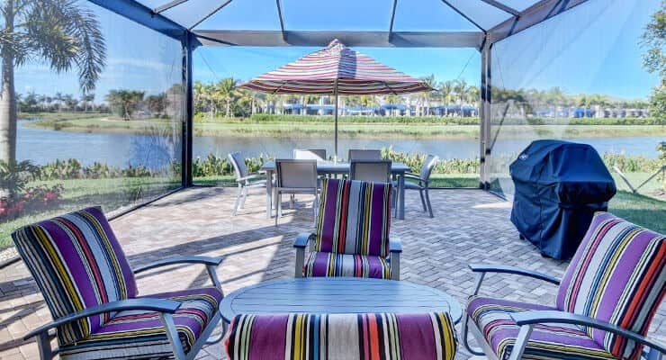 A POV of a view of a lake through a glass gazebo while lounging on a chair on a Valencia Palms real estate property.
