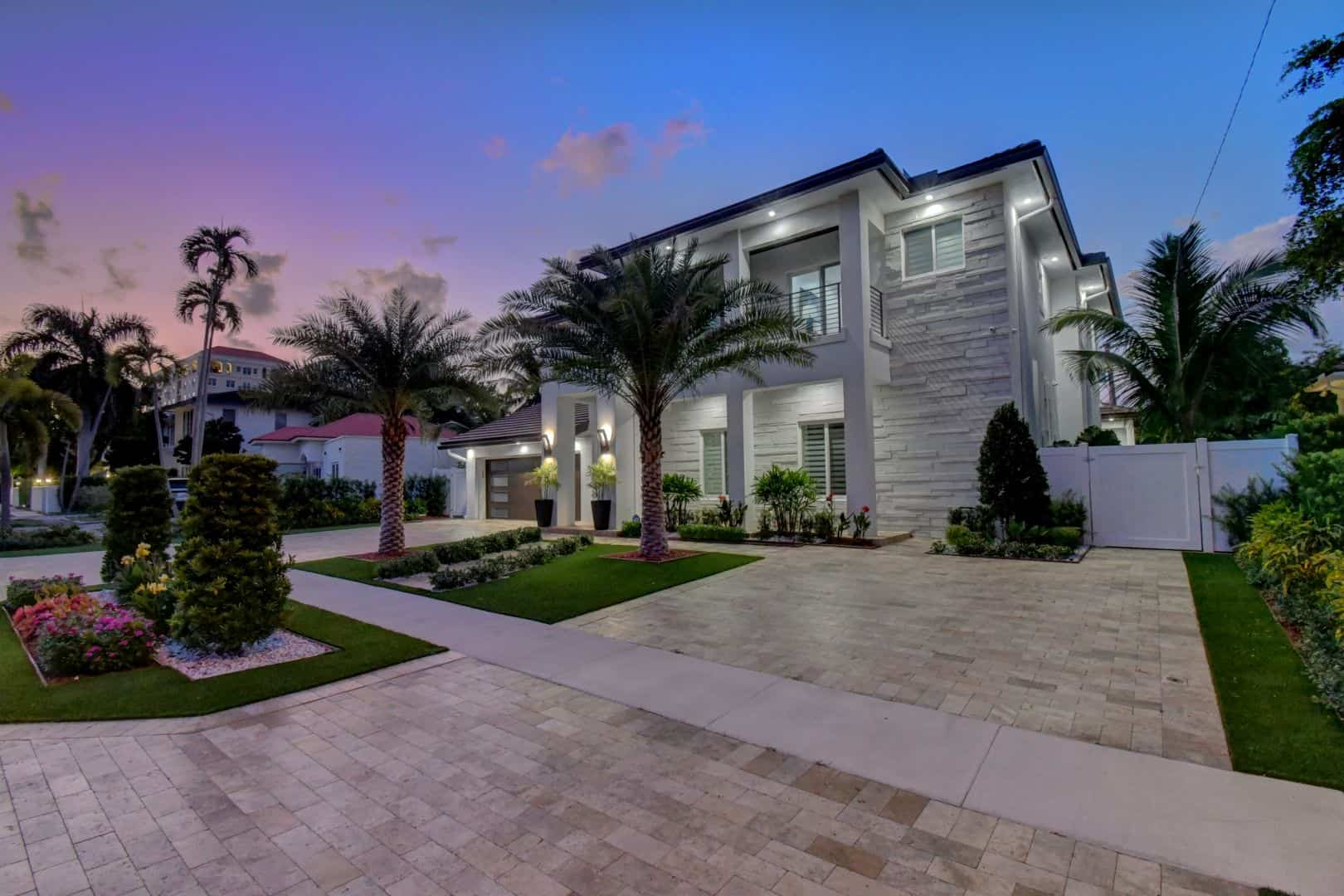 A luxurious two-story house with an attached garage and balconies that is an example of what our new construction opportunies in South Florida can offer you. Palm trees are in the front yard.