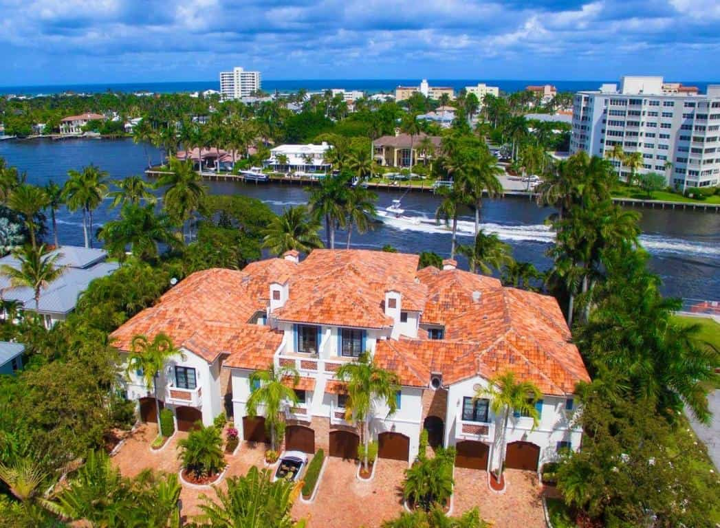 An aerial daytime view of Delray beach with a delray beach property and palm trees in the foreground and a river in the background.
