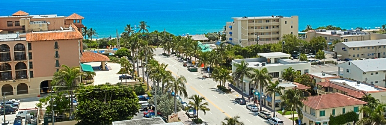 An aerial daytime view of Delray Beach closer to the Atlantic Ocean. A street with buildings lined with palm trees on its sides is shown.